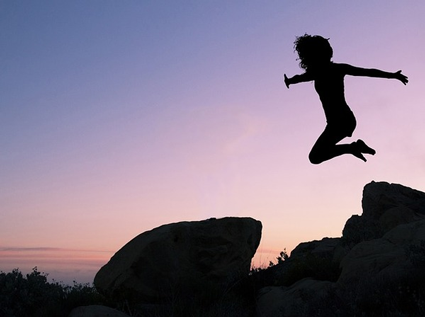 Image of woman jumping off rocks, symbolzing the jump organizations take into social media marketing plans.
