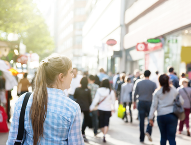 Woman standing in crowd downtown. Use local SEO tactics and inbound marketing tools to attract customers in places like Detroit Michigan.